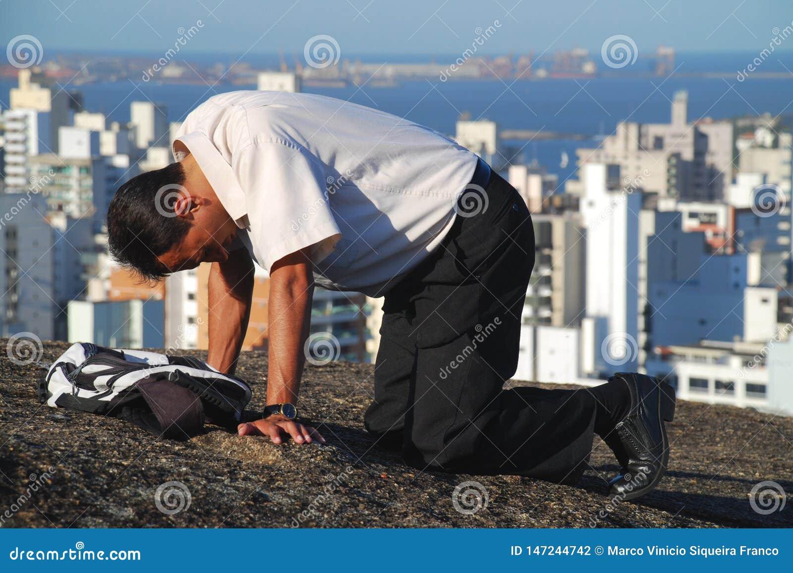 Hombre que ruega sobre la montaña en el Brasil