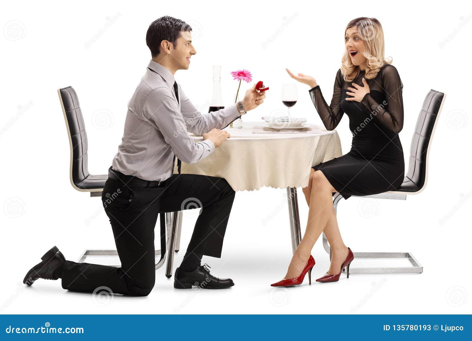 Hombre que se arrodilla y que propone con un anillo a una mujer en una tabla de cena