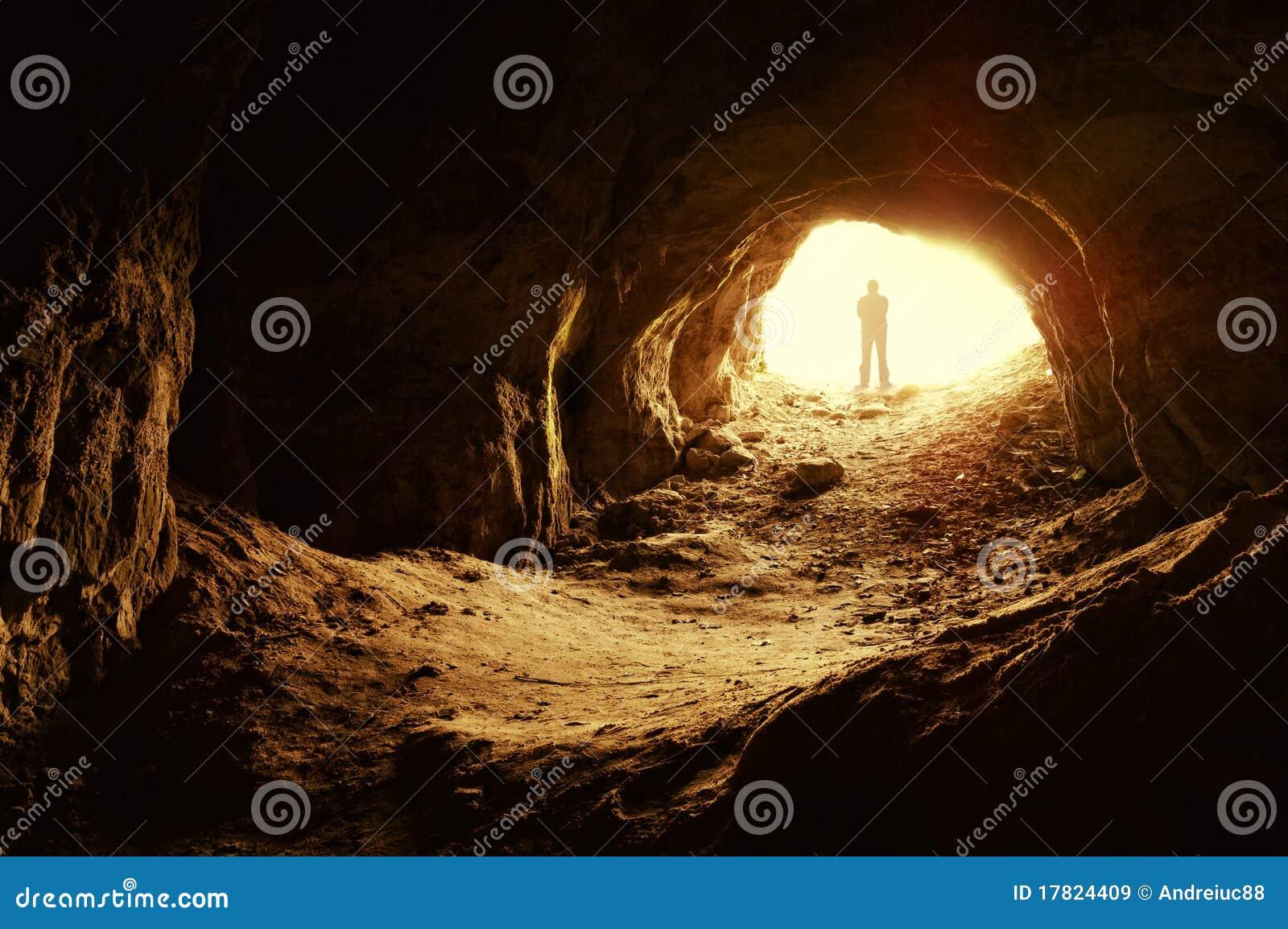 Hombre que se coloca delante de una entrada de la cueva