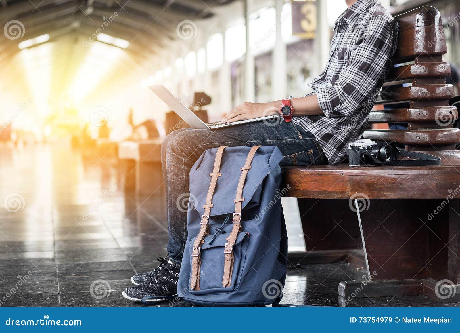 Hombre que se sienta con el ordenador portátil bolso del viaje en la estación de tren