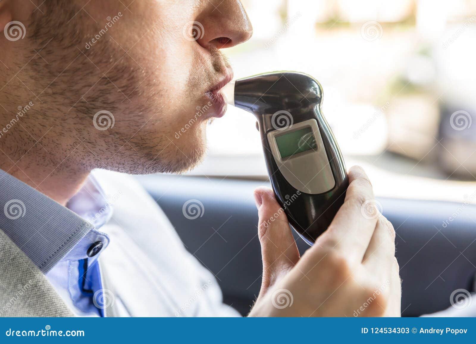 Hombre que se sienta dentro del coche que toma la prueba de alcohol