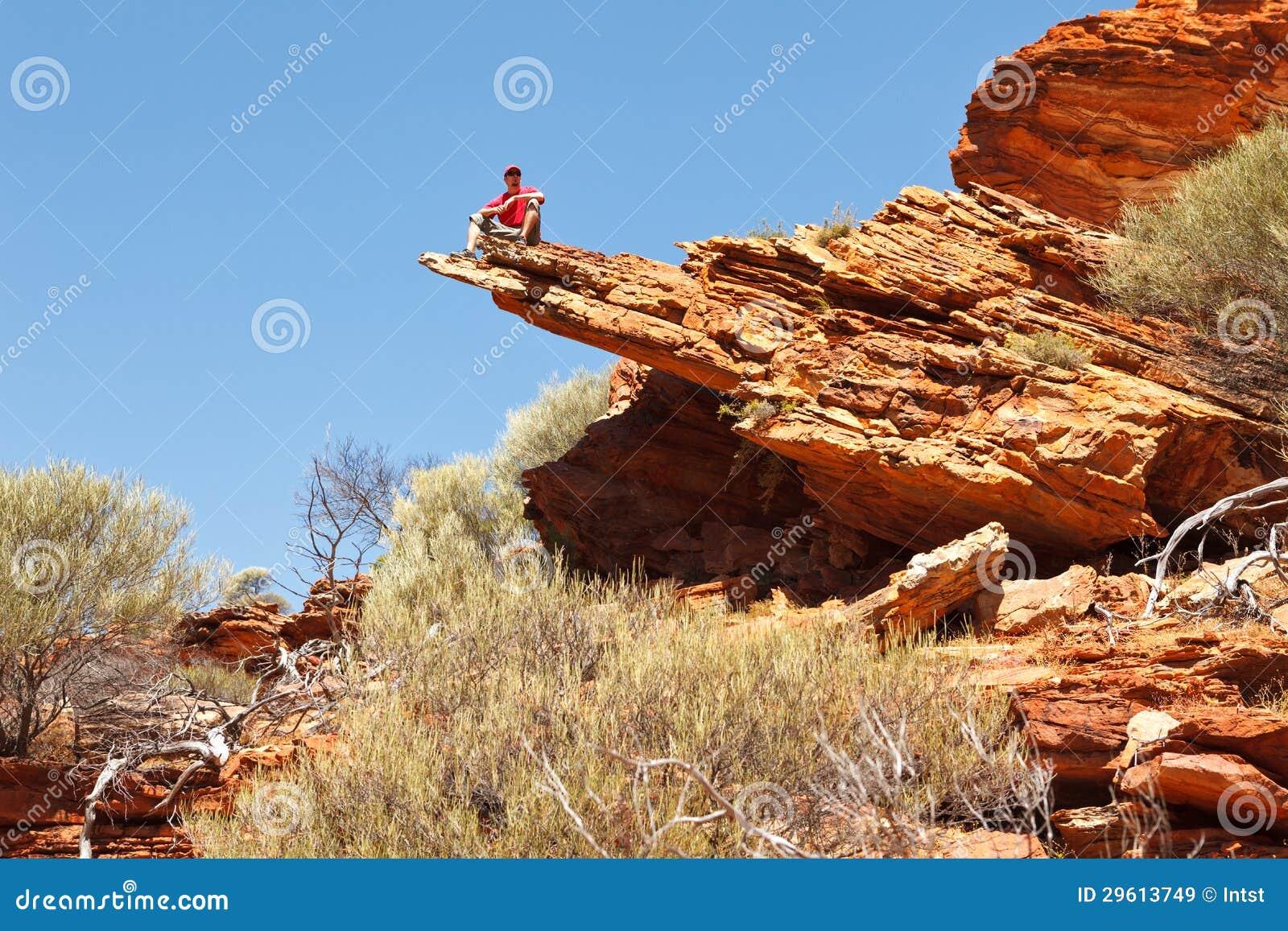 Hombre que se sienta en el borde de la roca