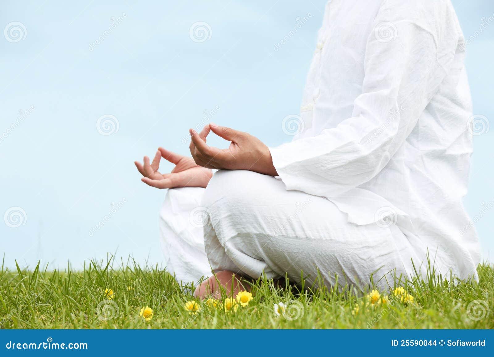Hombre que se sienta en la posición de loto meditativa