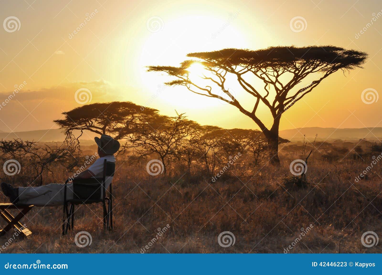 Hombre que se sienta en la puesta del sol