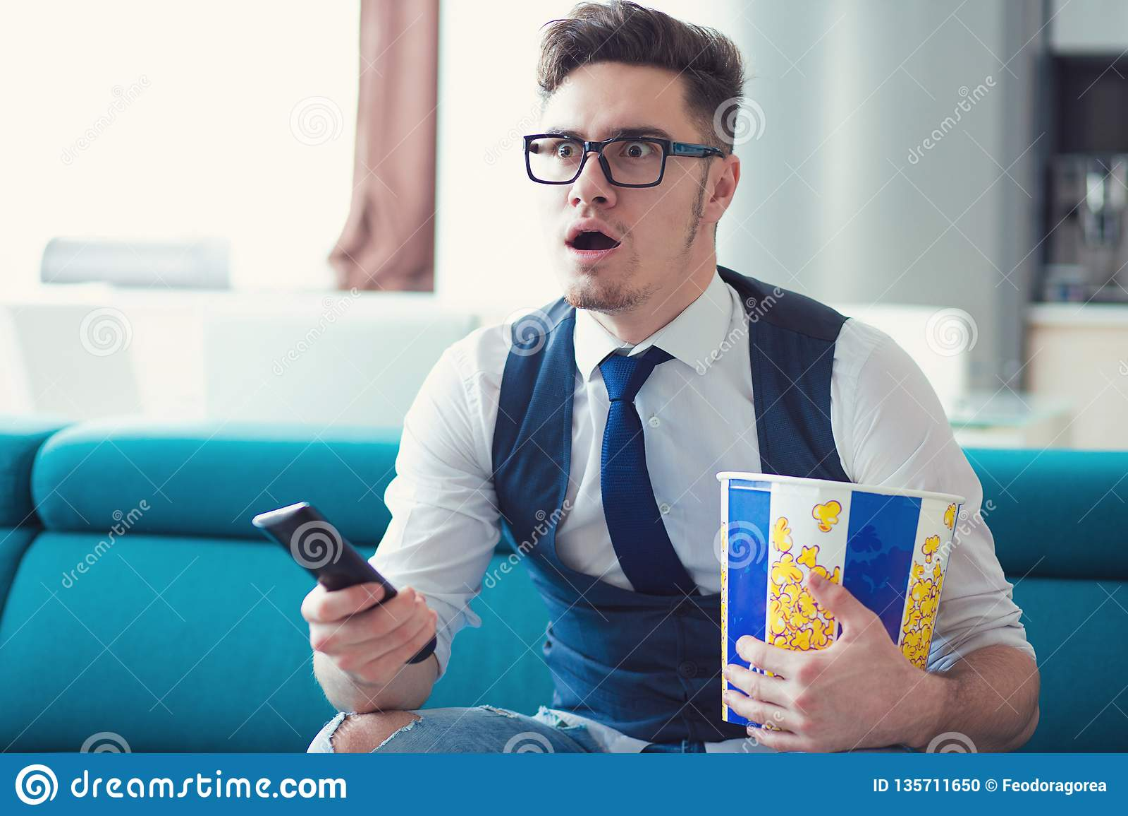 Hombre que se sienta en un sofá, TV de observación, sosteniendo la caja del telecontrol y de las palomitas, sorprendida en lo que