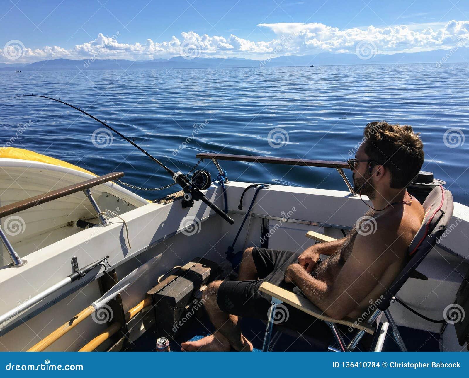 Hombre que se sienta y que se relaja en la popa de su barco como él pesca para