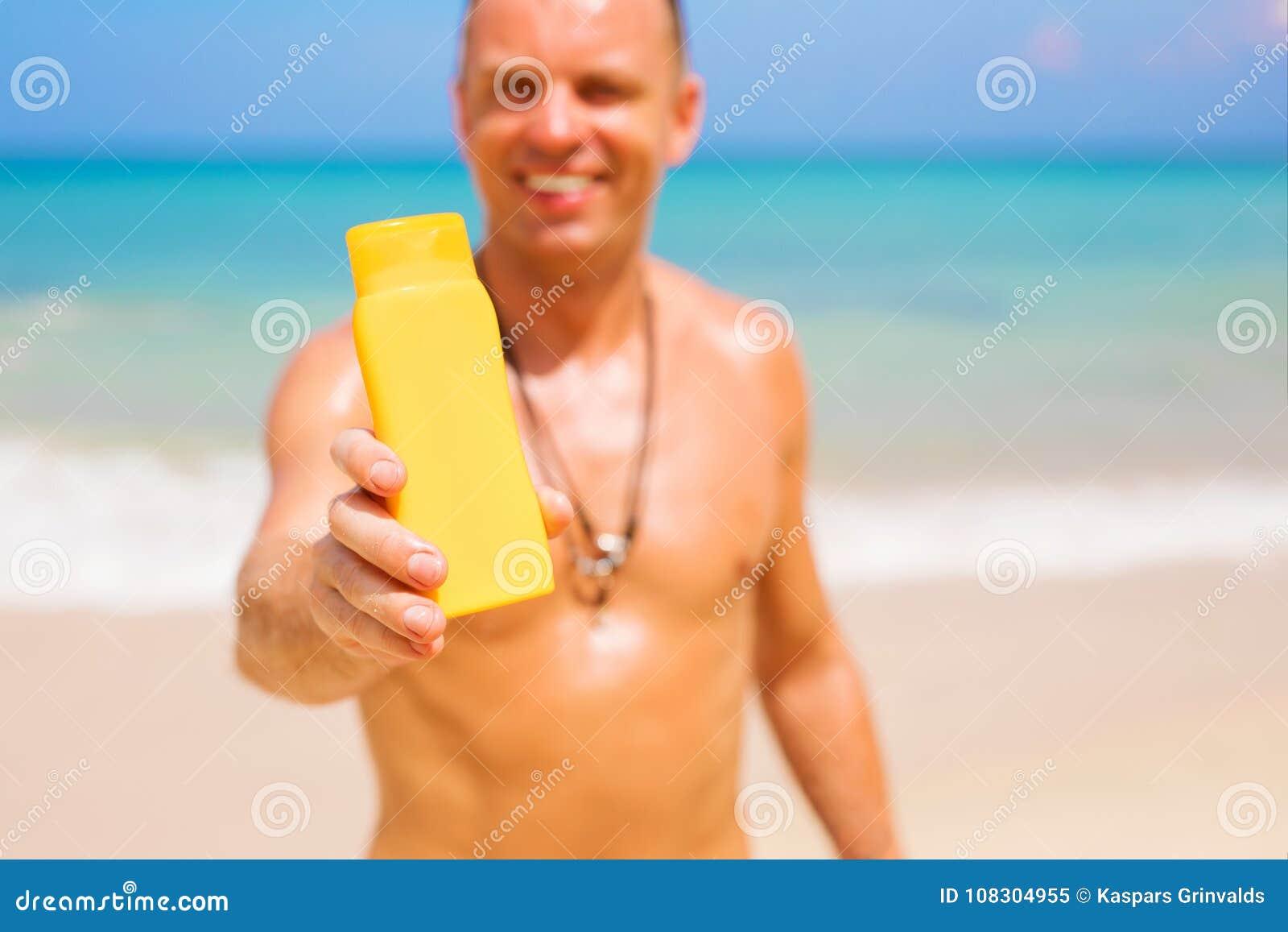 Hombre que sostiene la botella de la protección solar Foco en la botella del producto de la muestra
