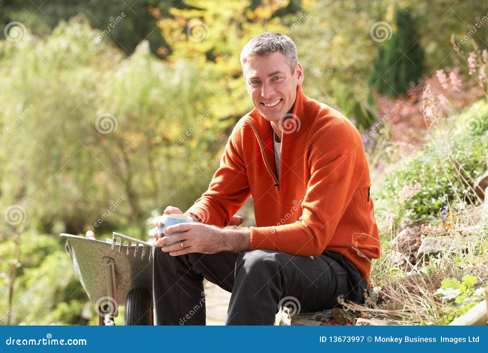Hombre que tiene descanso para tomar café mientras que trabaja al aire libre