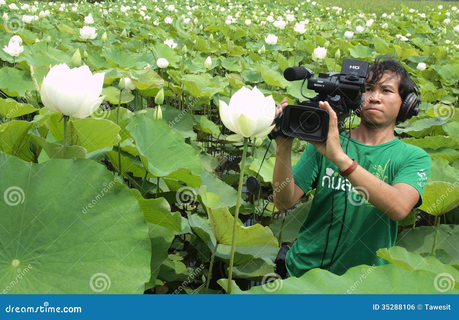 Hombre que toma el video en granja del loto