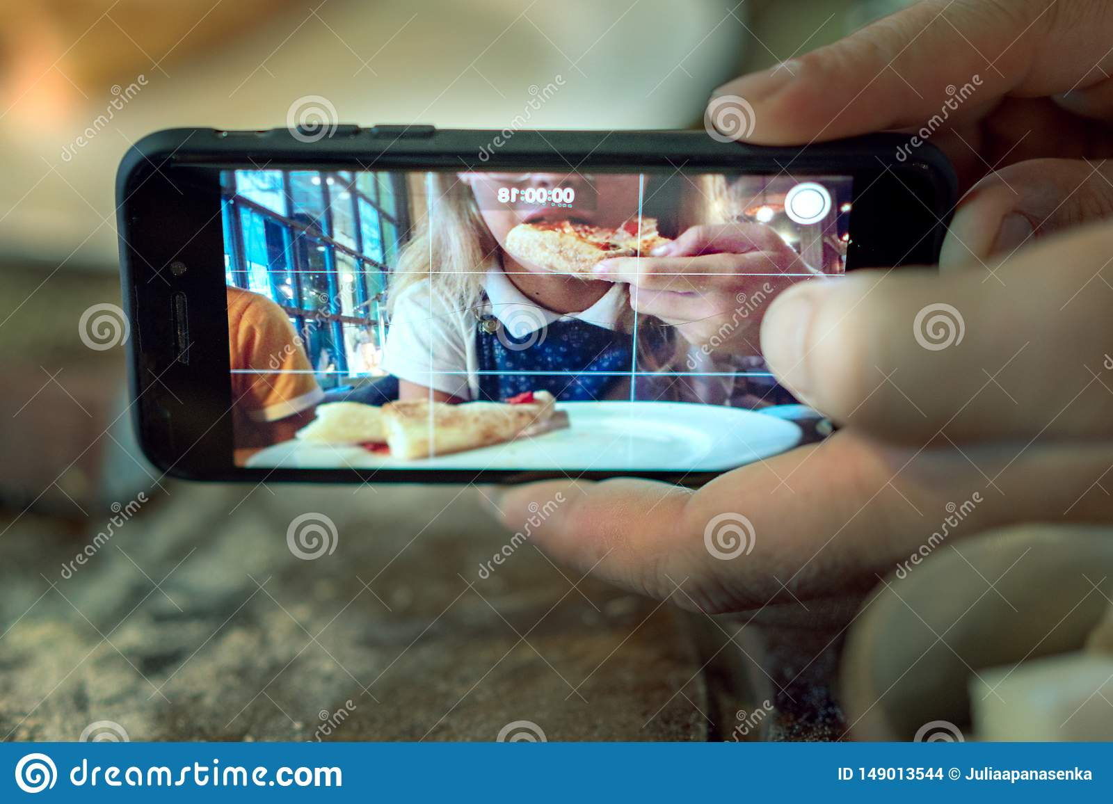 Hombre que toma la foto de una muchacha que come la pizza