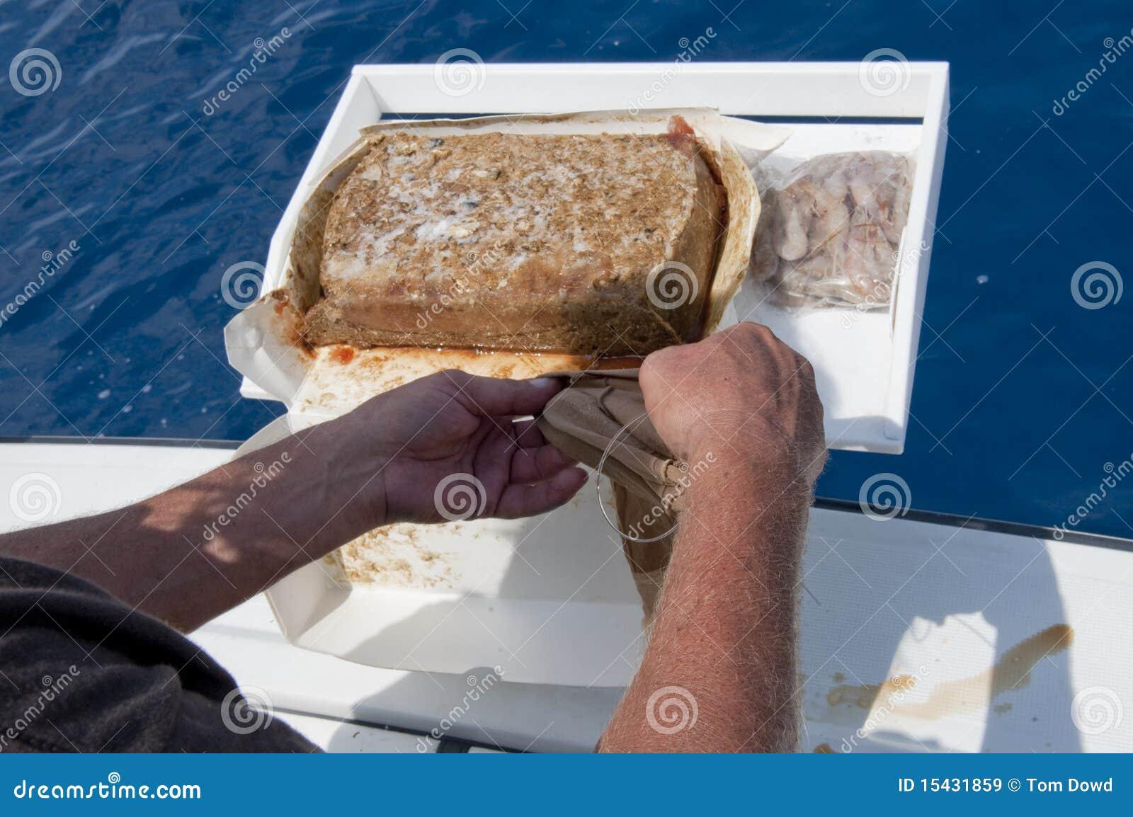 Hombre que trabaja con cebo de los pescados