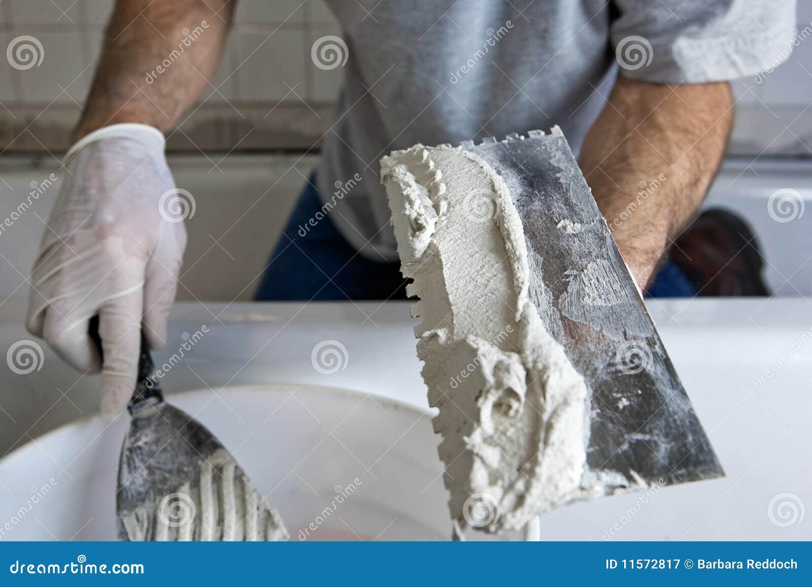 Hombre que trabaja con la paleta y el mortero que embaldosan una pared