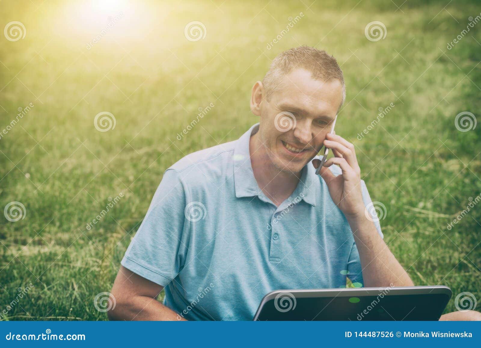 Hombre que trabaja con su ordenador port?til en el parque