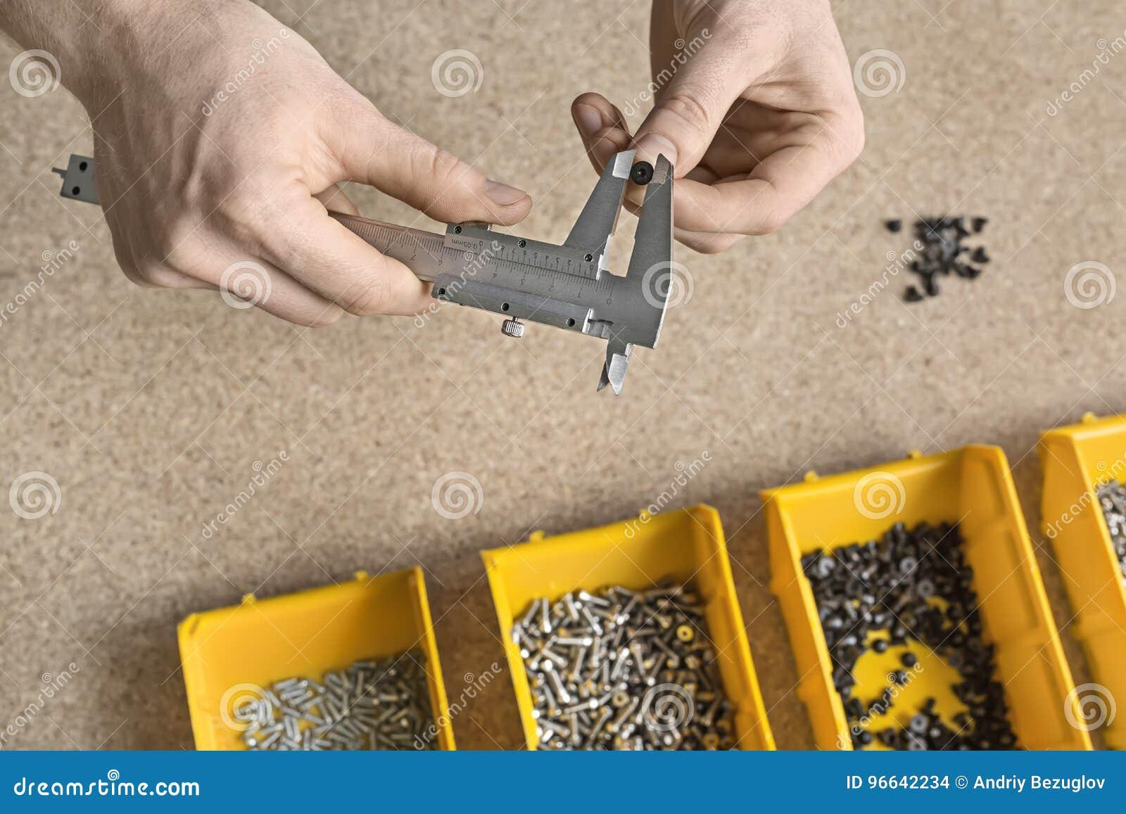 Hombre que usa el calibrador en taller