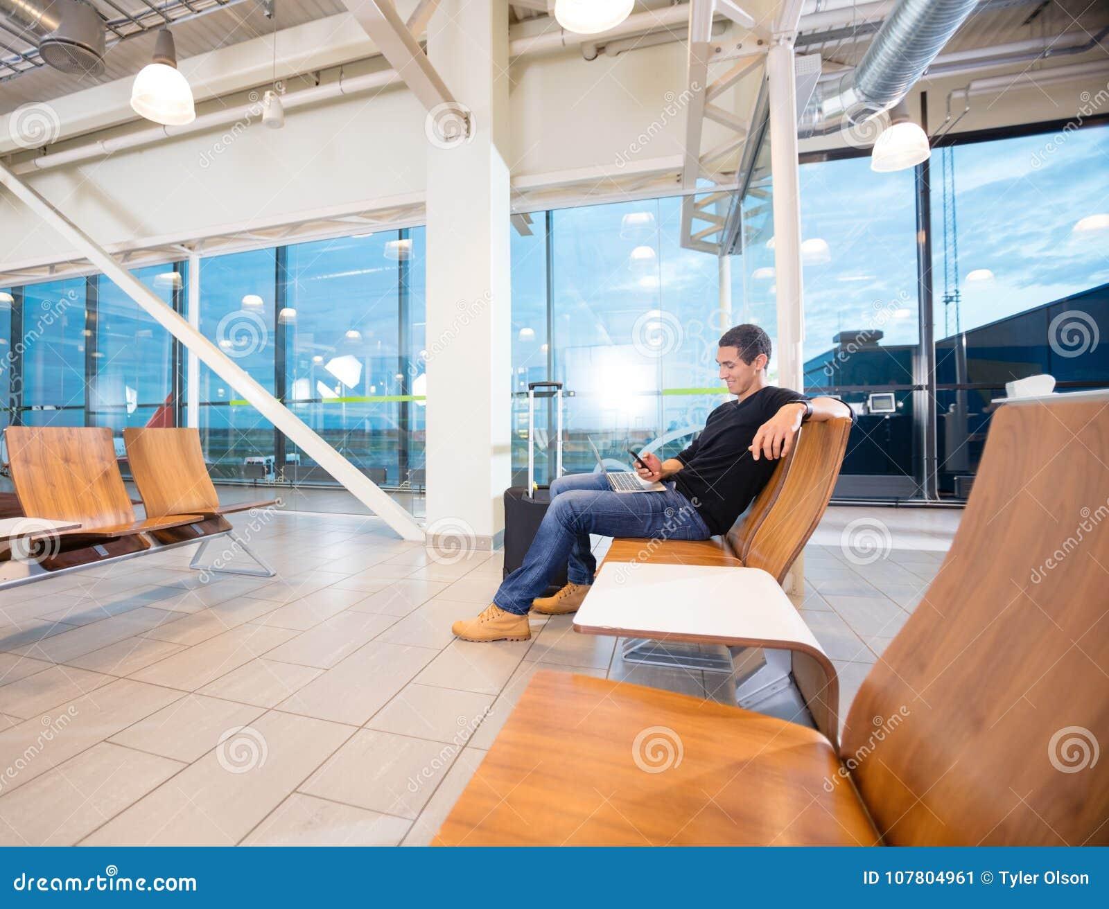 Hombre que usa el teléfono móvil mientras que espera su vuelo