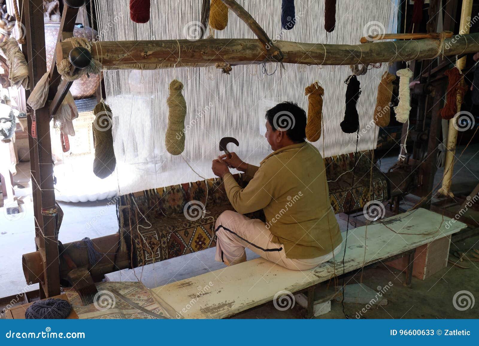 Hombre que usa el telar durante la fabricación hecha a mano de la alfombra