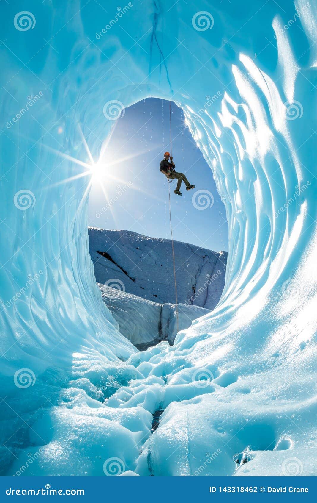Hombre rappelling en la entrada de la cueva de hielo del glaciar en las montañas de Alaska