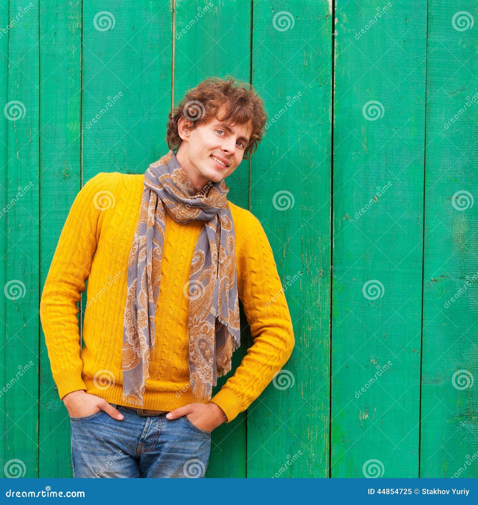 Hombre rizado sonriente en suéter y bufanda amarillos en vagos de madera verdes