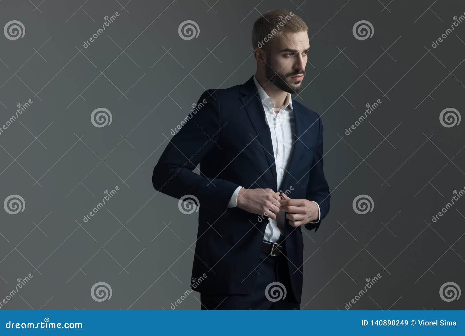 Hombre rubio en el traje que ajusta su chaqueta de salón