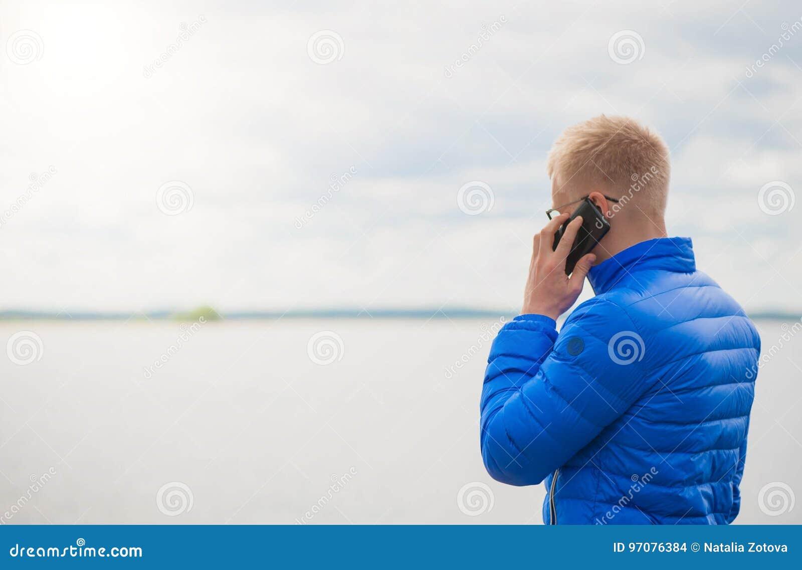 Hombre rubio que usa el teléfono móvil en el lago