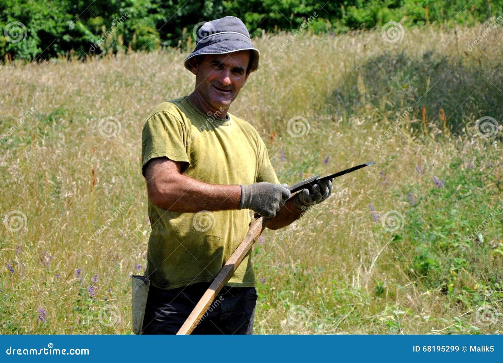 Hombre rural que usa la guadaña