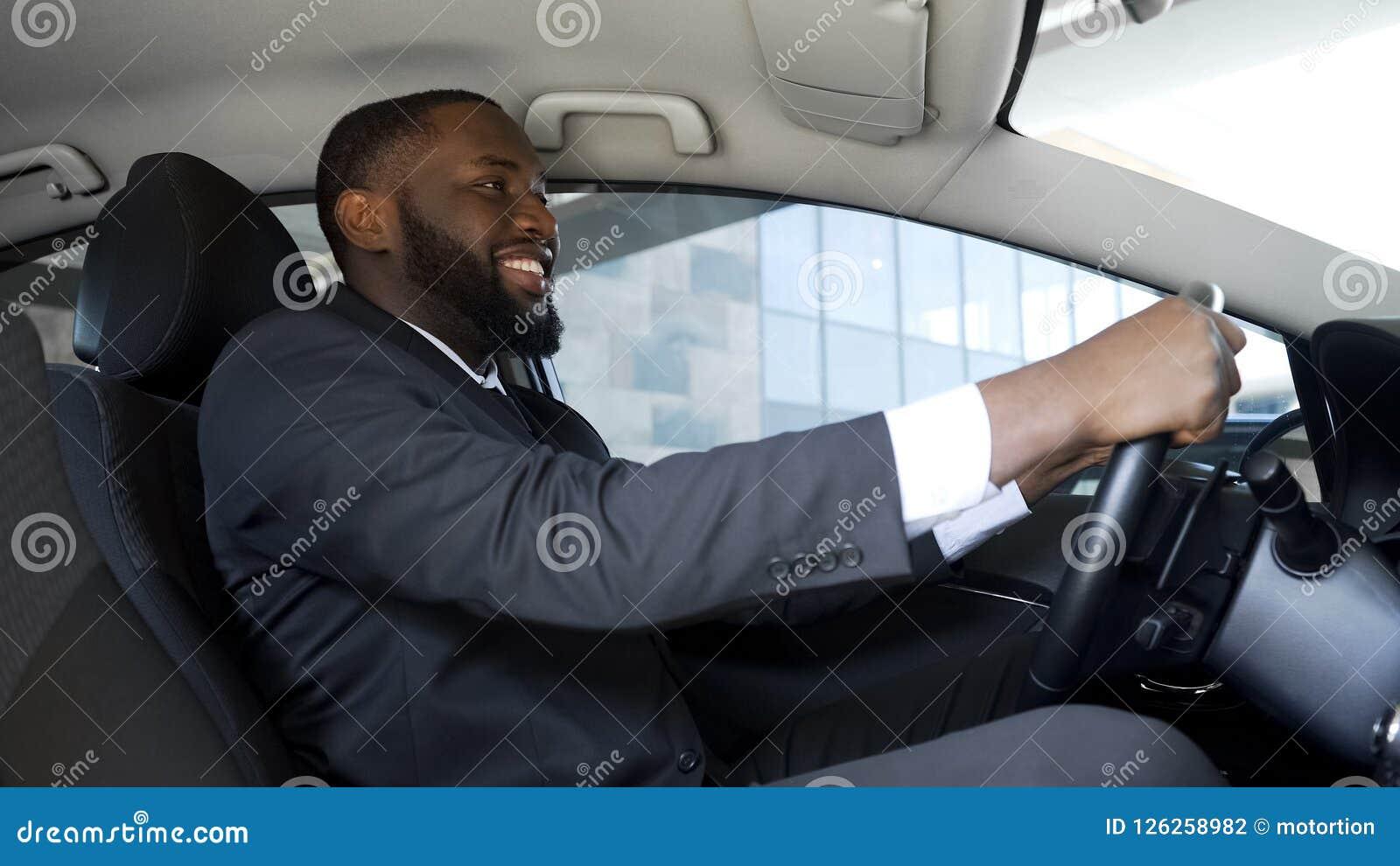 Hombre satisfecho en el traje de negocios que se sienta en el coche, compra acertada, felicidad