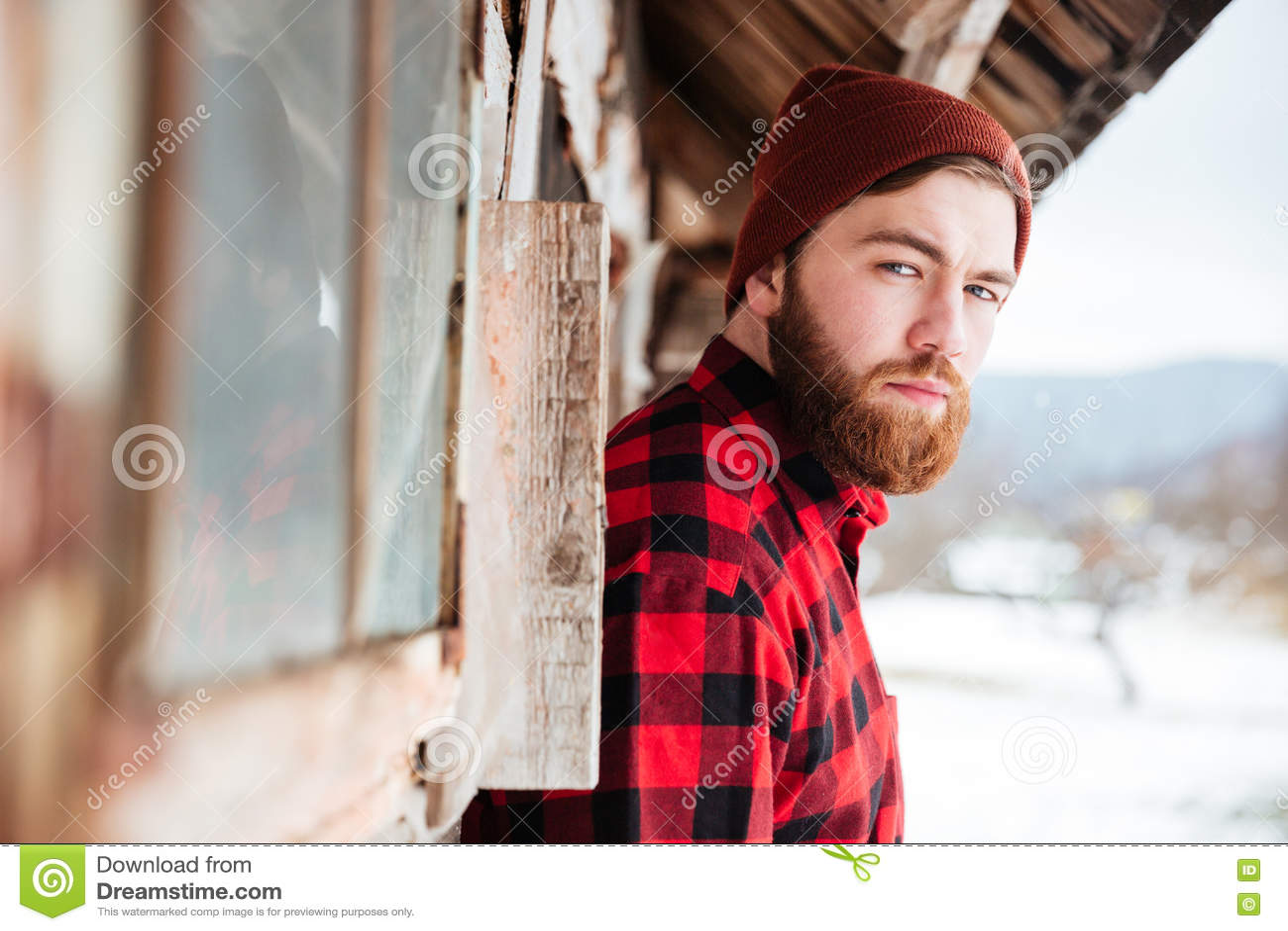 Hombre serio en casa de madera vieja en el pueblo