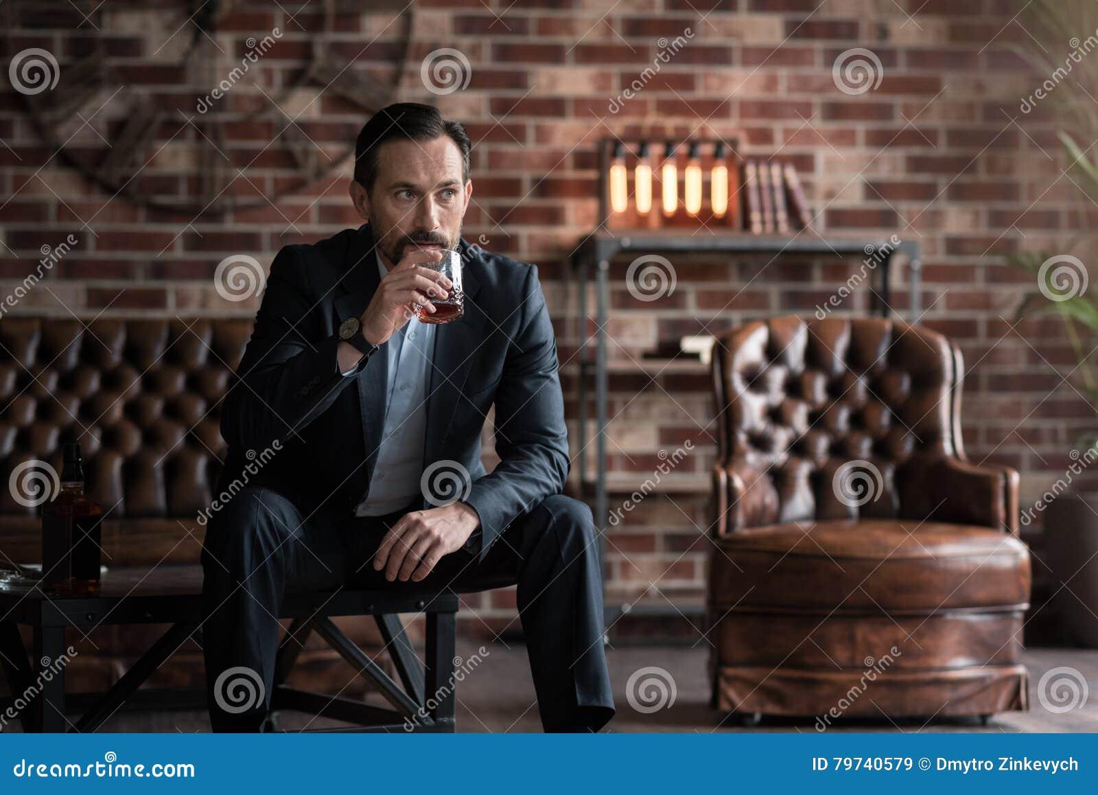 Hombre serio hermoso que toma un sorbo de whisky