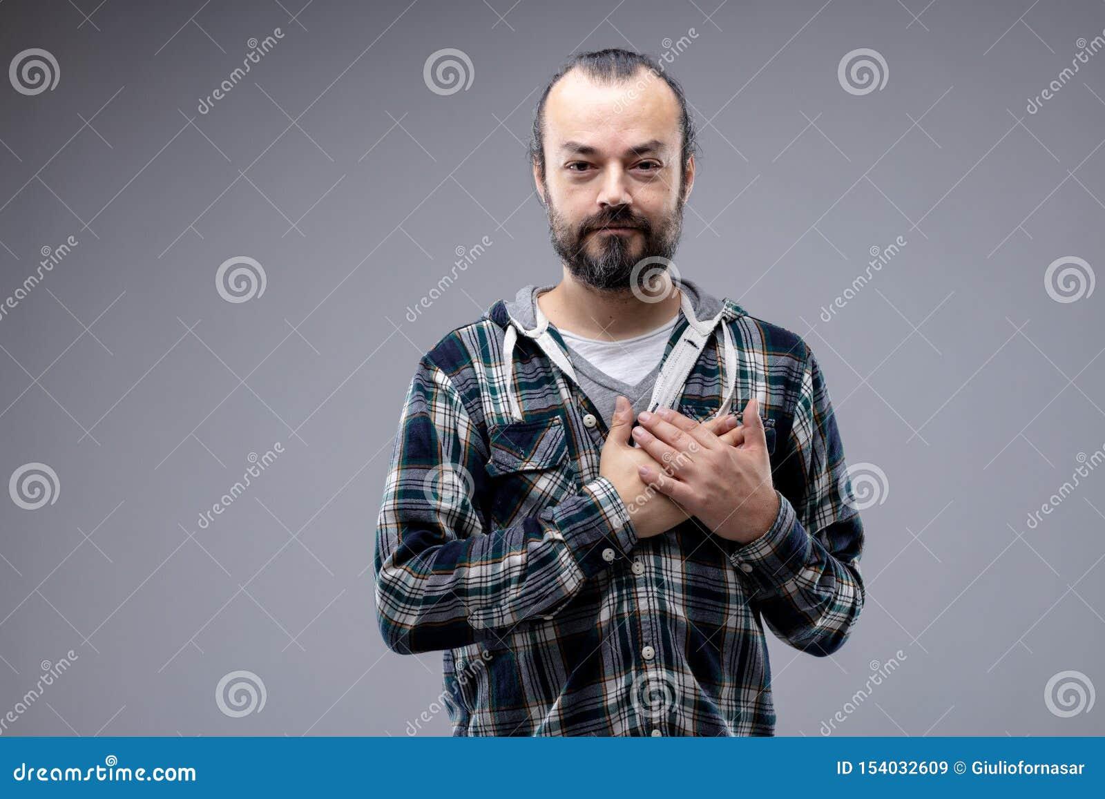 Hombre sincero que cruza sus manos sobre su corazón