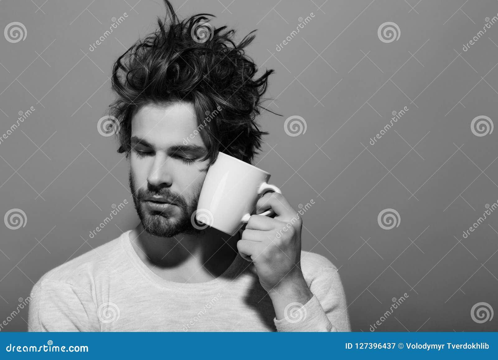 Hombre soñoliento con la taza de té o de café