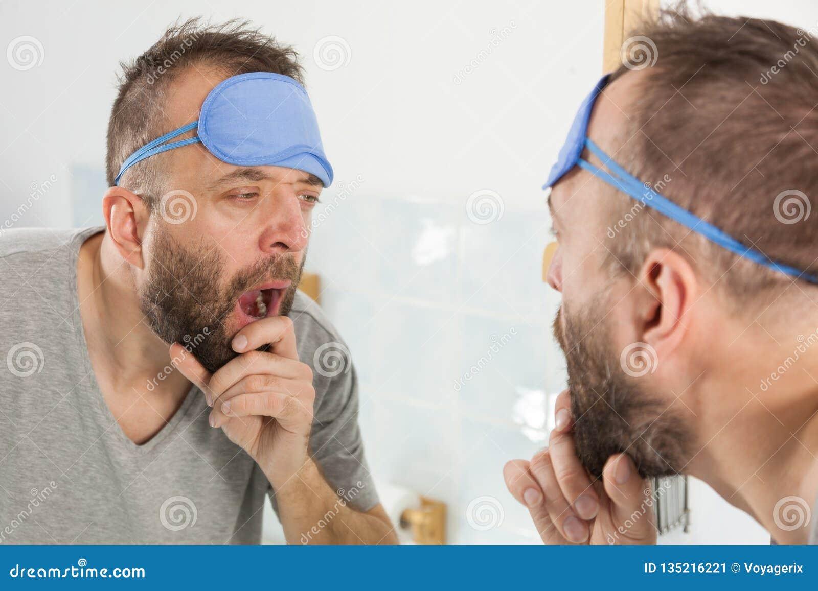 Hombre soñoliento que mira el espejo y que bosteza