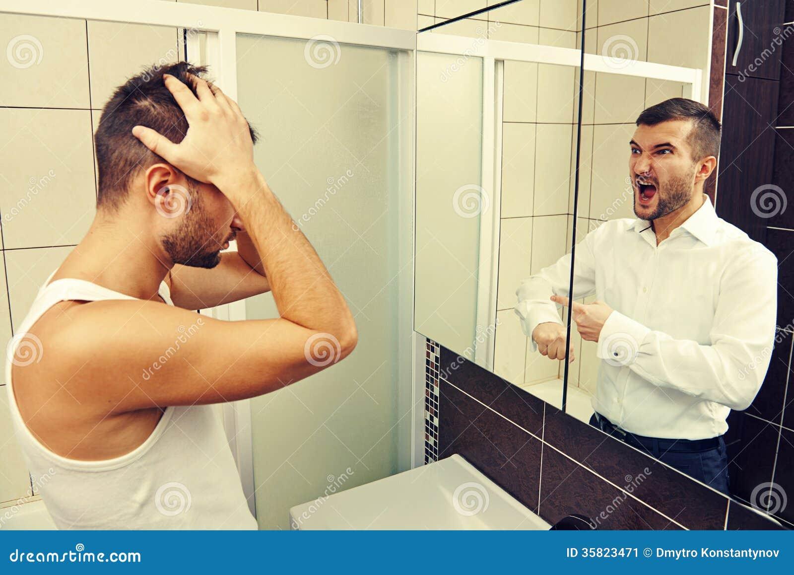 Hombre soñoliento que mira en el espejo