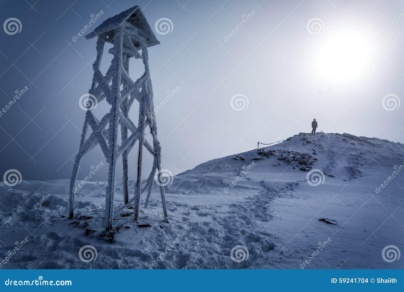 Hombre solitario en el top de la montaña en invierno