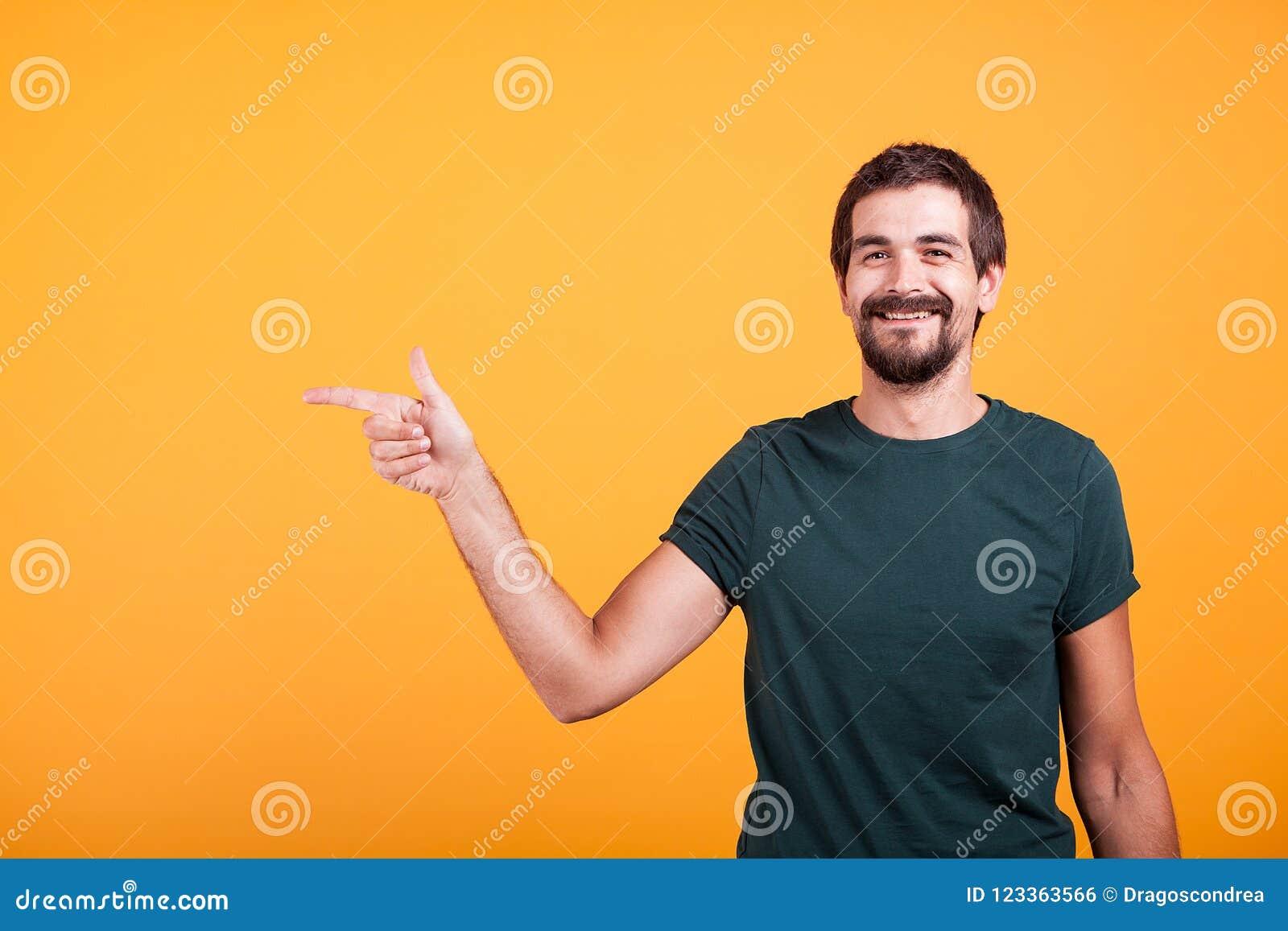 Hombre sonriente alegre que señala en su derecha en el copyspace