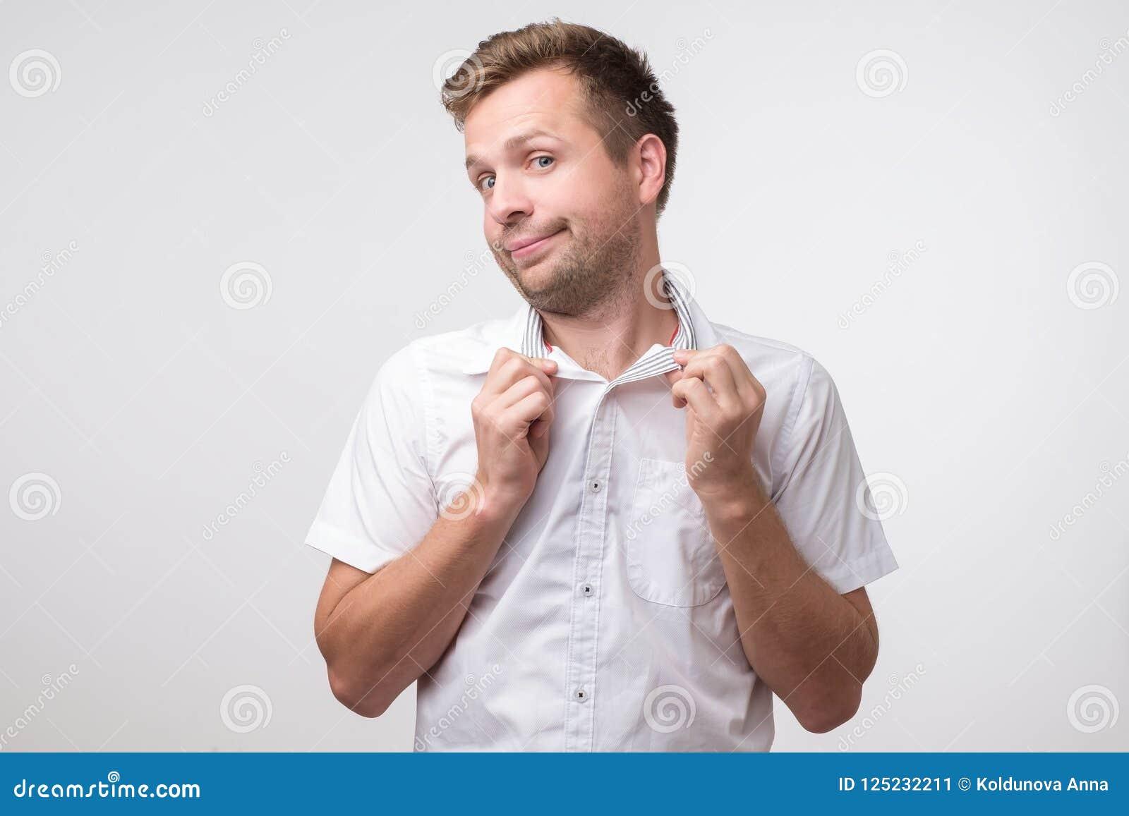 93e4bdeb0 Hombre sonriente lindo caucásico poting Comportamiento alegre y juguetón  Retrato de un individuo joven en la camisa blanca en fondo ligero