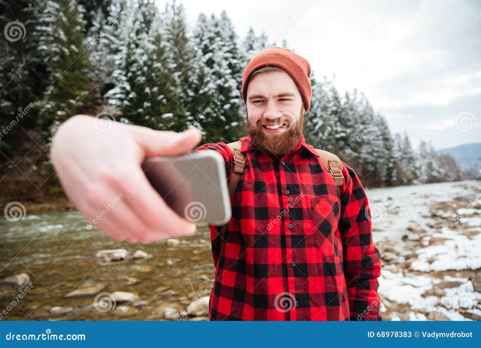 Hombre sonriente que hace la foto del selfie al aire libre