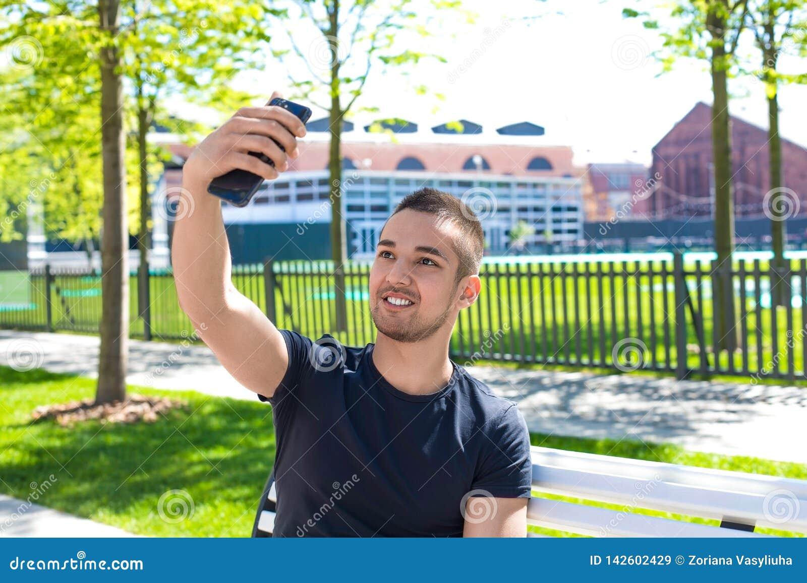 Hombre sonriente que tiene llamada video en línea en smartphone durante tiempo libre al aire libre