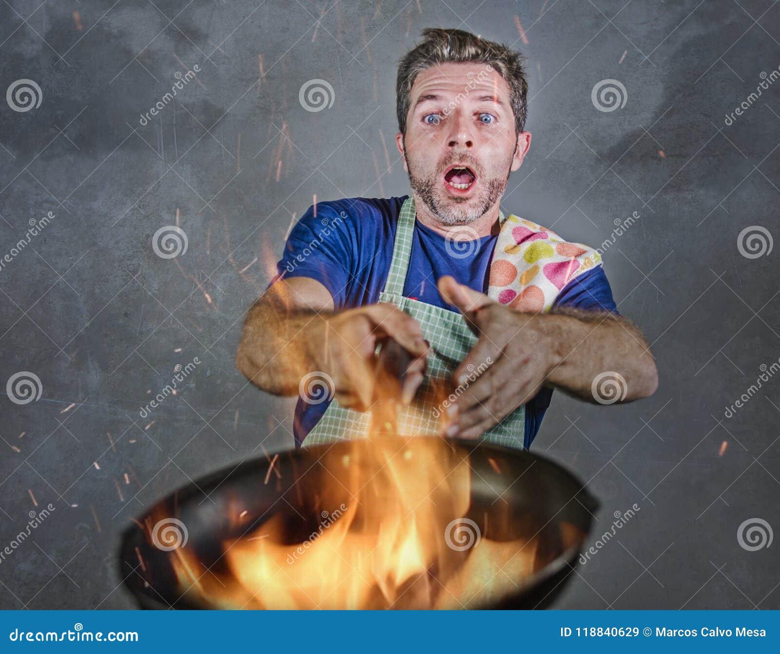Hombre sucio chocado con el delantal que sostiene la cacerola en el fuego que quema la comida en desastre de la cocina y terrible