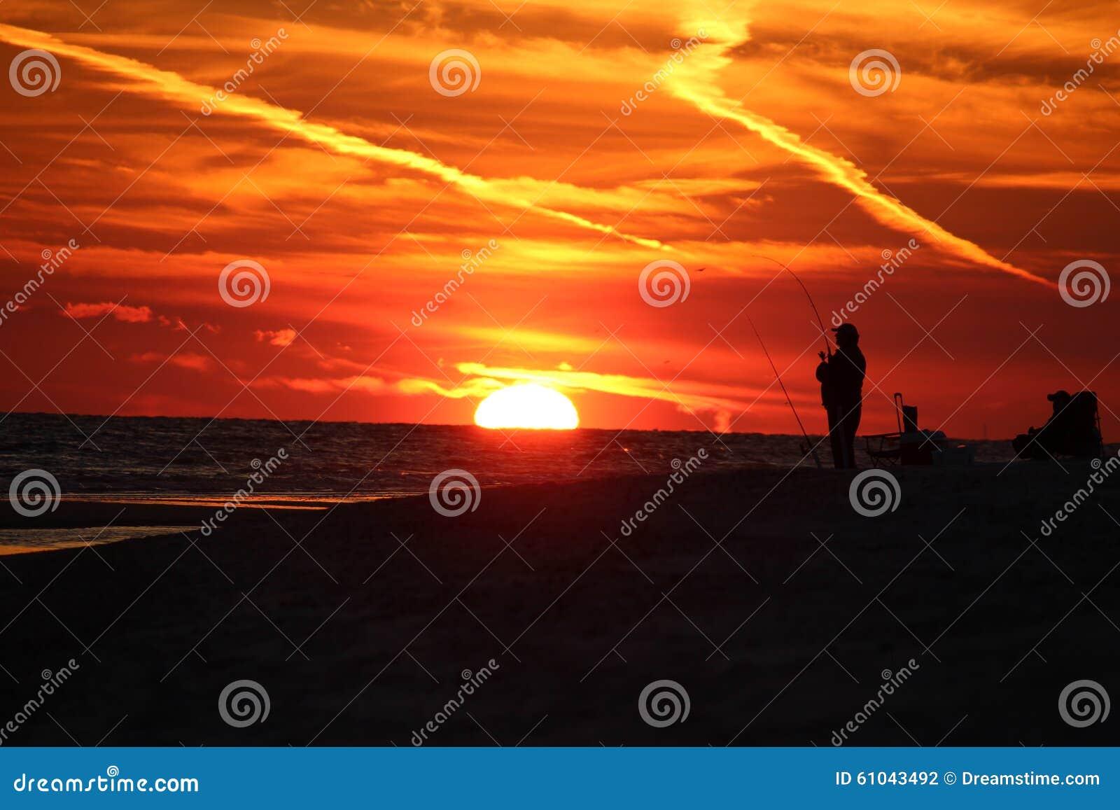 Hombre surfcasting en la puesta del sol en Alabama