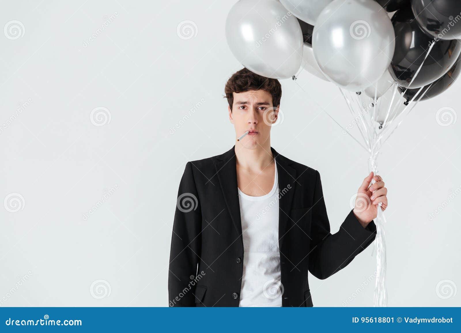 Hombre tranquilo que sostiene los balones de aire y que fuma el cigarrillo