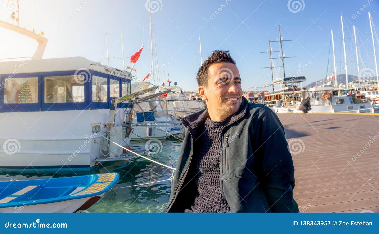 Hombre turístico turco joven que sonríe durante puesta del sol en el puerto deportivo de Bodrum, Turquía Barcos de navegación, ma