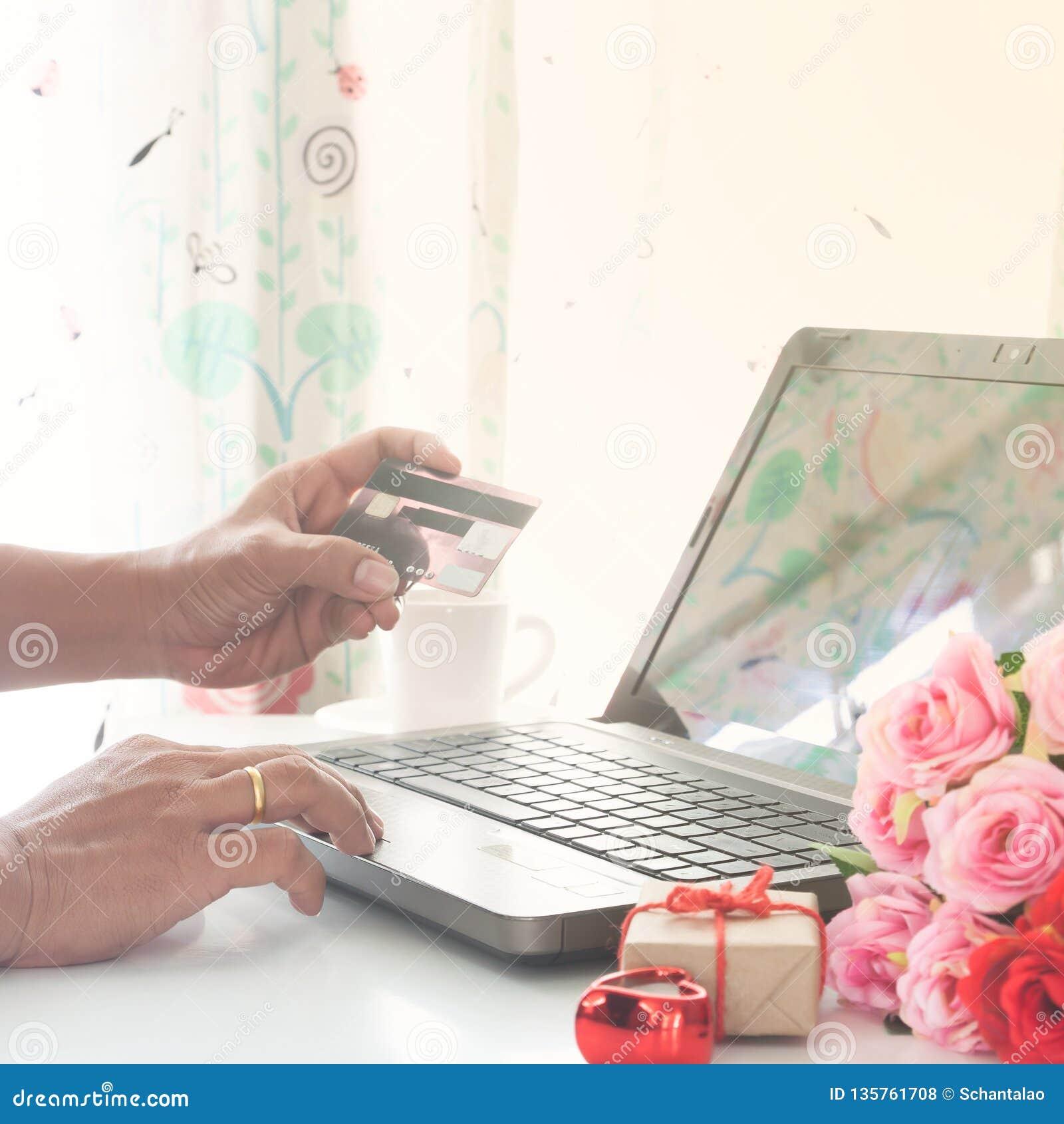 Hombre usando el ordenador y tarjeta de crédito con el regalo y las rosas en la tabla, haciendo compras en línea valentines