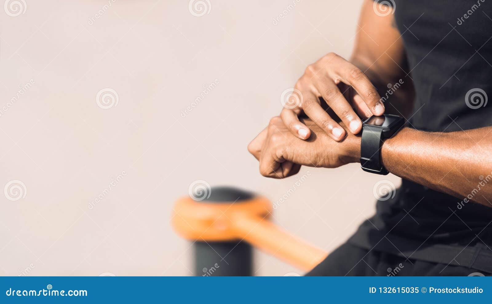Hombre usando el reloj elegante negro, comprobando ritmo cardíaco