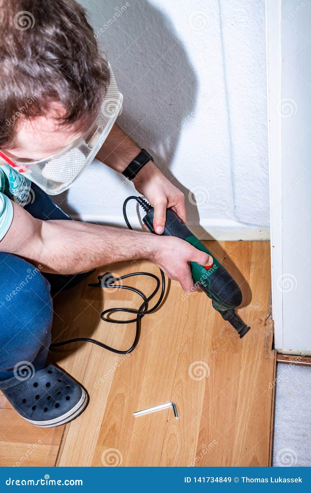 Hombre usando su herramienta multi eléctrica en la lamina