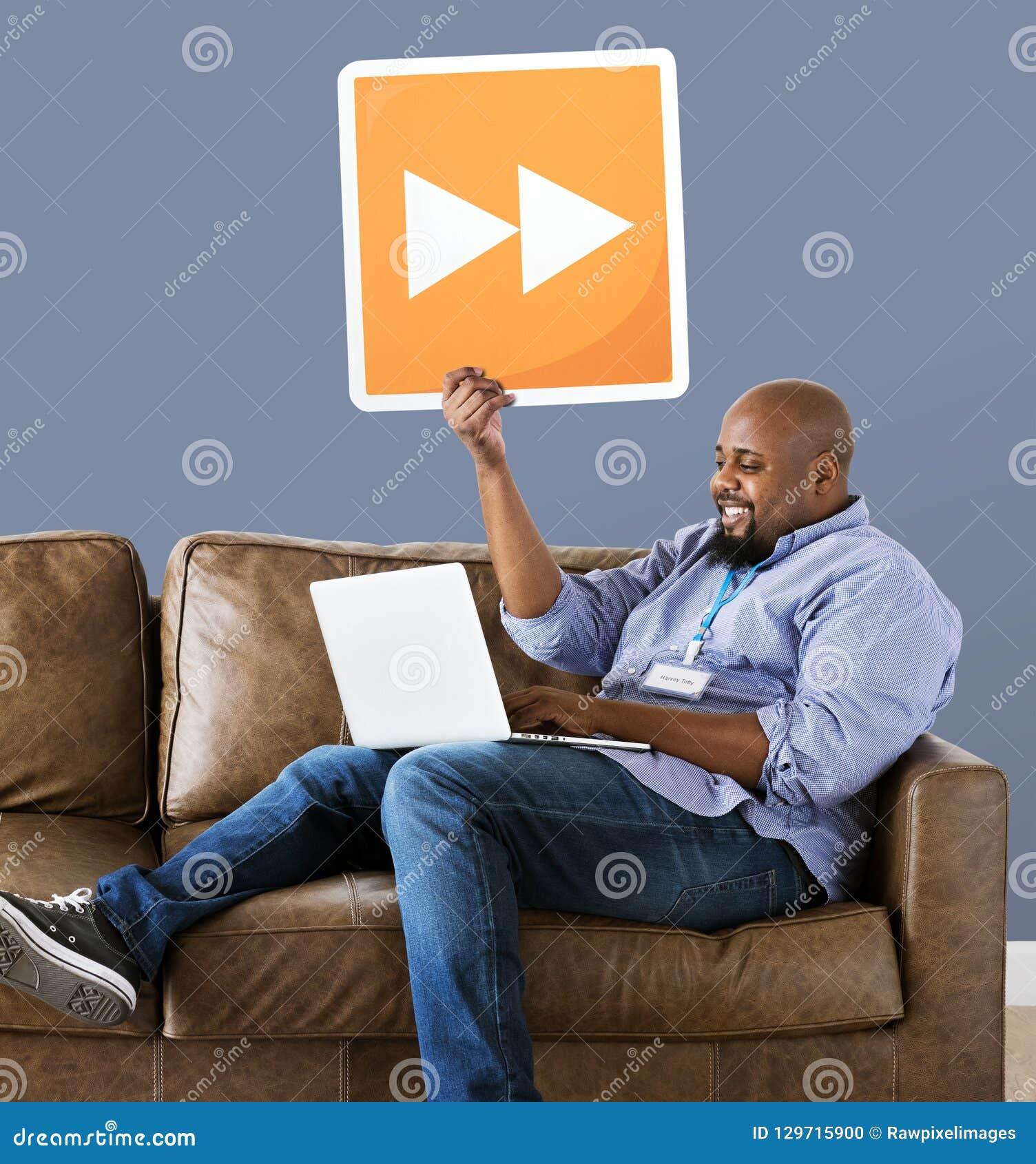 Hombre usando un ordenador portátil y sostener un botón delantero rápido
