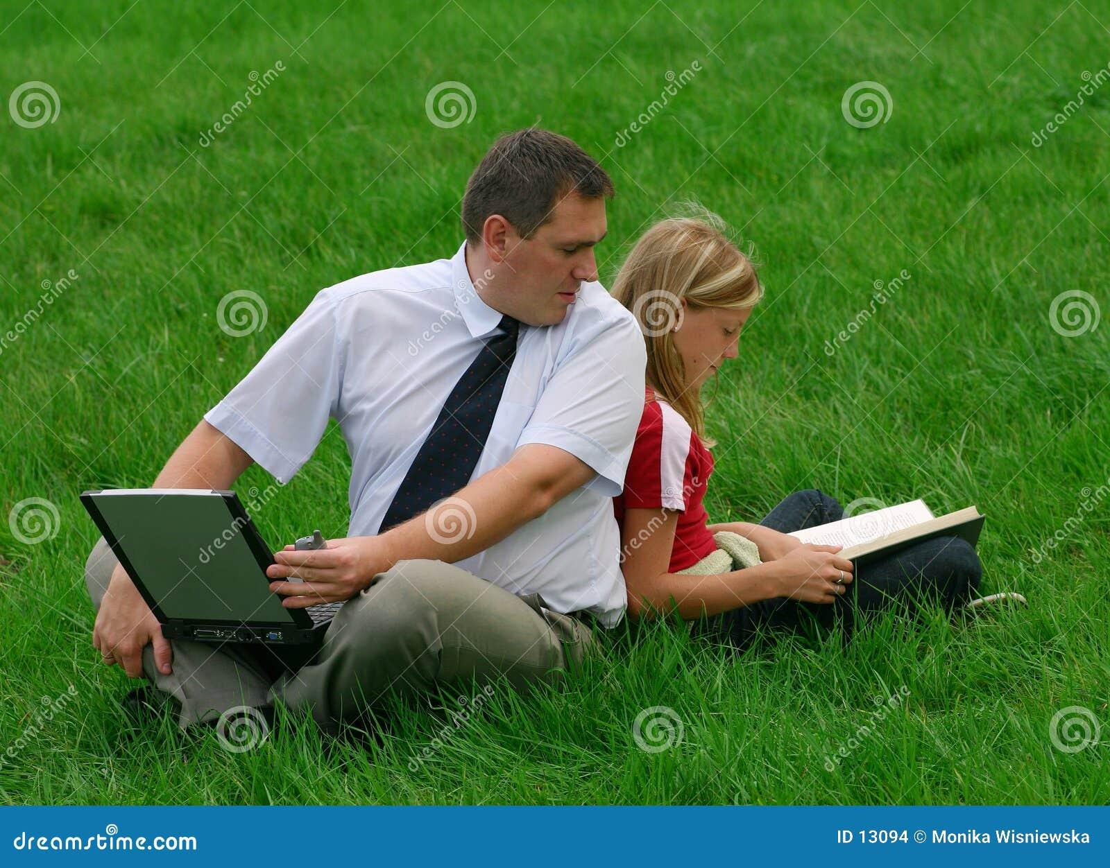 Hombre y muchacha que se sientan en la hierba