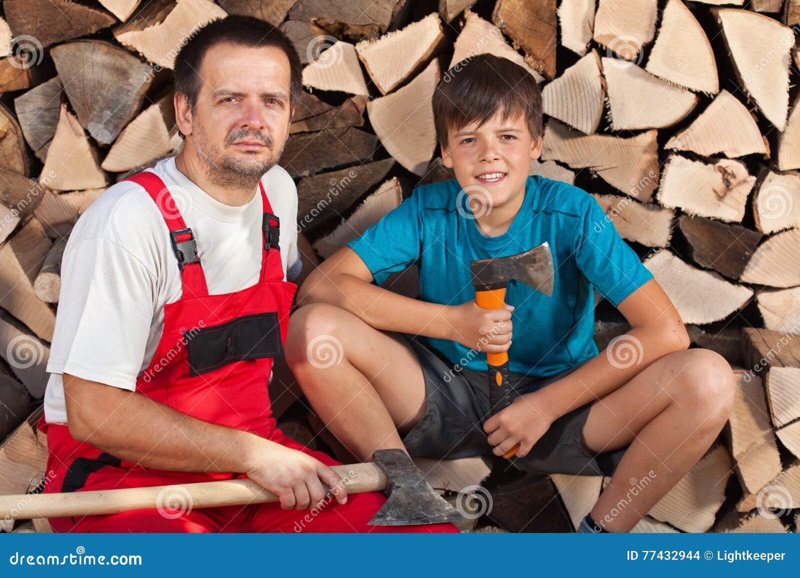 Hombre y muchacho que se sientan junto delante de la madera tajada