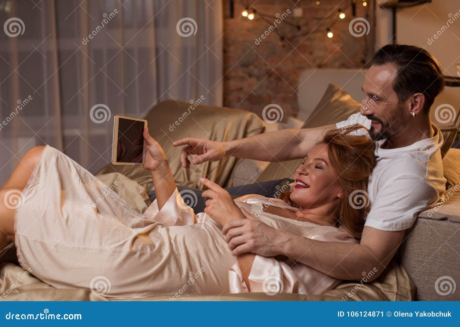 Hombre y mujer alegres que usa el artilugio en casa