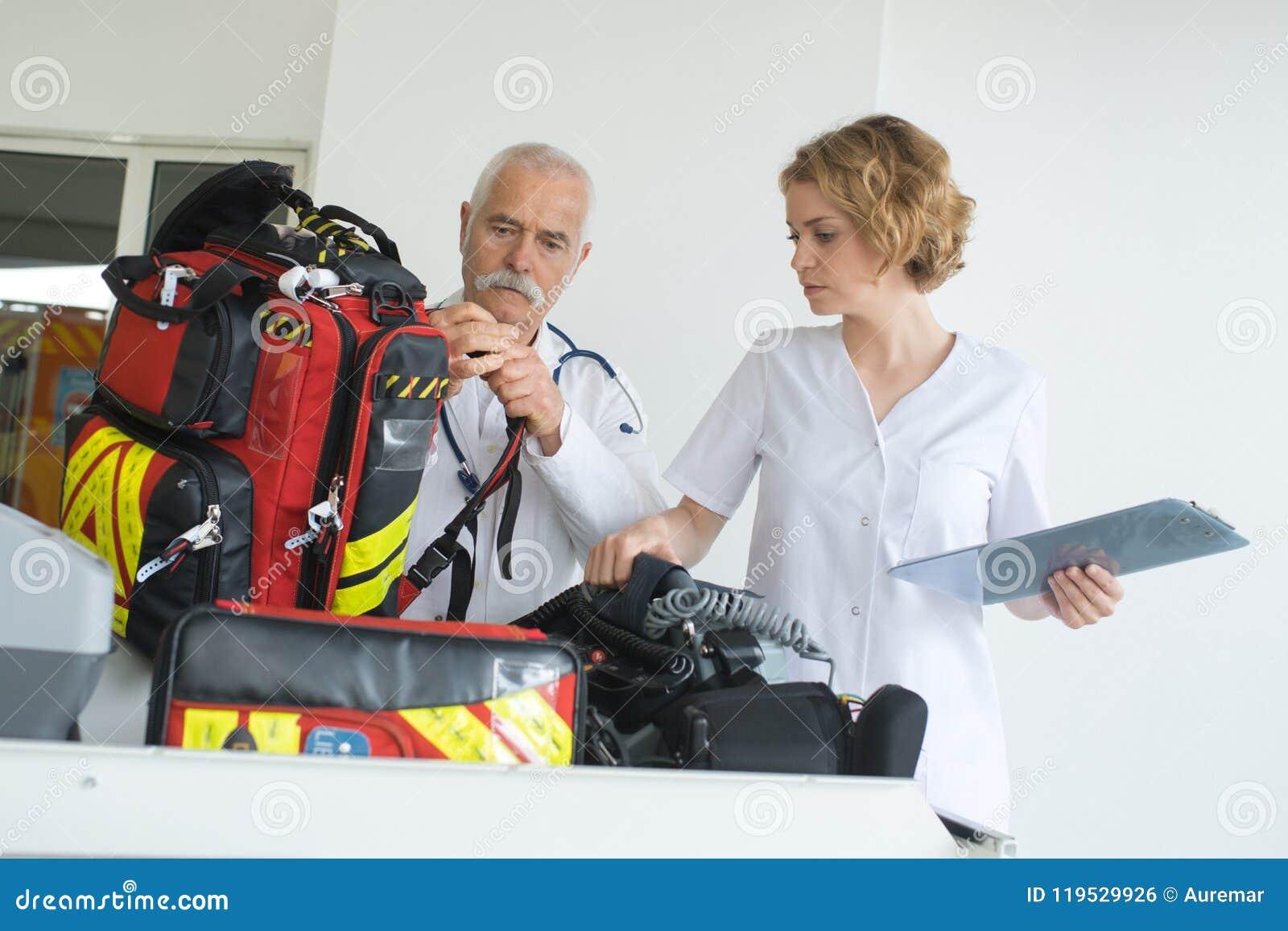 Hombre y mujer de la ambulancia que comprueban el engranaje entre las intervenciones