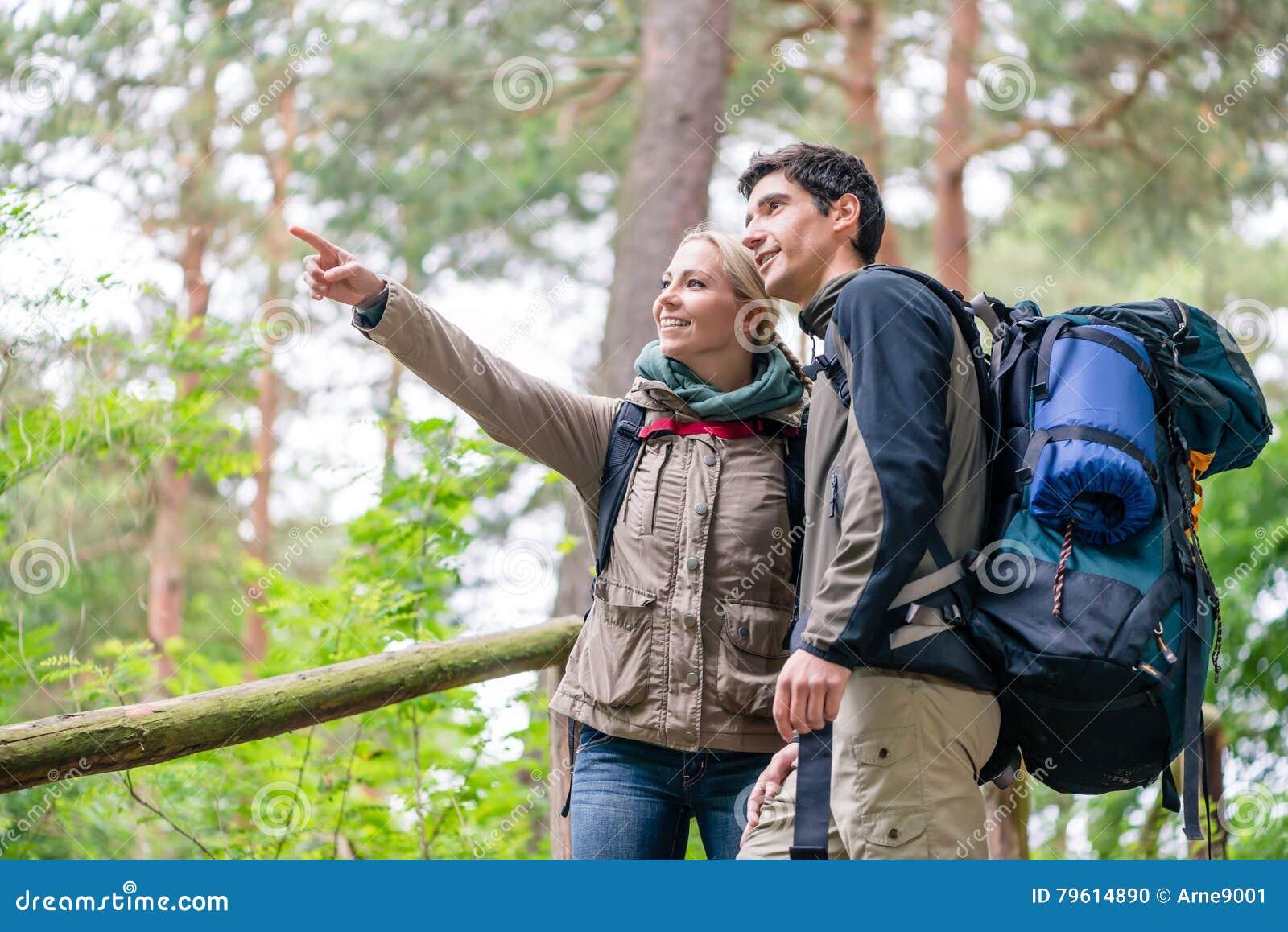 Hombre y mujer en el alza que busca el rastro derecho en mapa